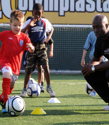 Child playing Football with a coaching watching him. County Sport Partnership