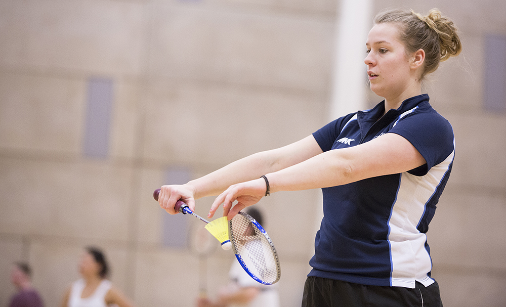 A young women about to serve in badminton