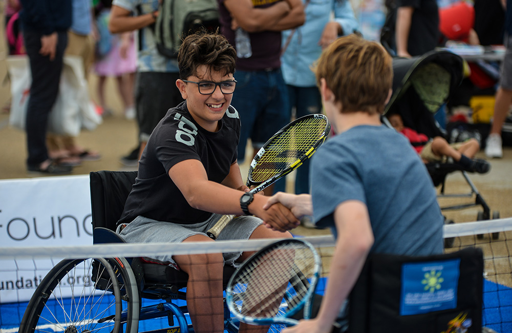 two wheelchair tennis players shaking hands after a game