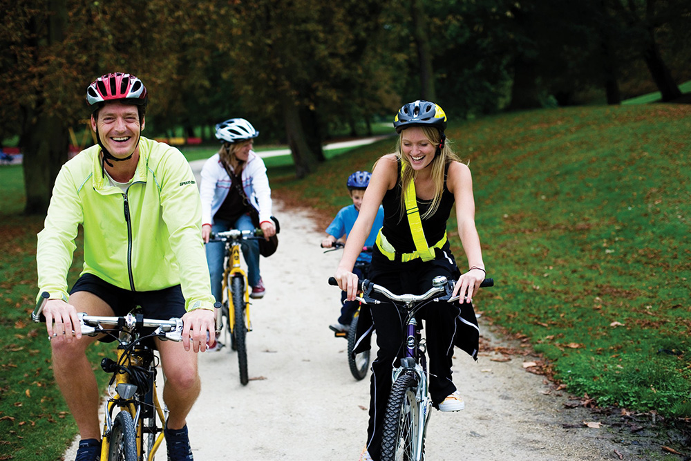A family cycling through a park