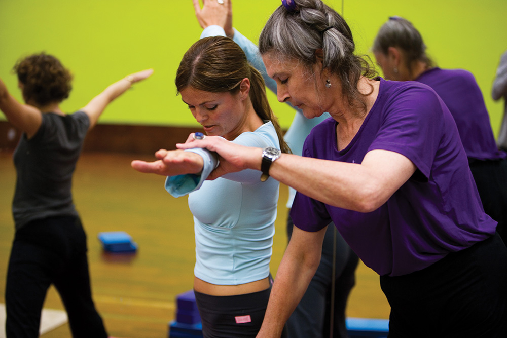 Woman being assisted by yoga instructor