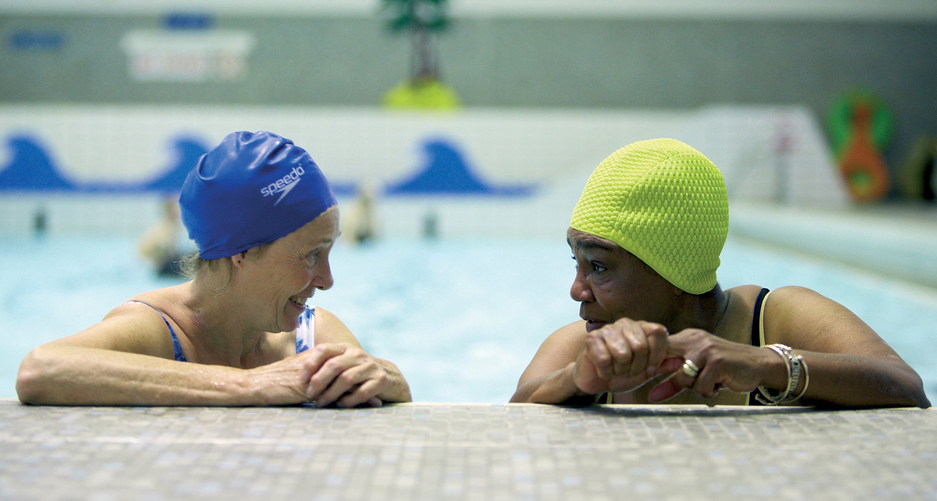 Two women talk whilst on the side of a swimming pool. Insight